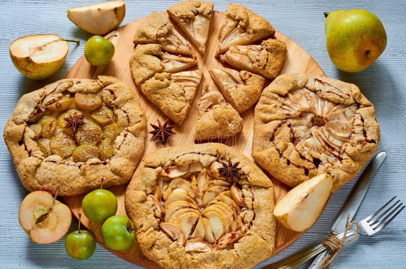与用葡萄酒刀子和叉子装饰的巧克力顶部的自创果子馅饼在具体背景 素食galette 免版税库存图片