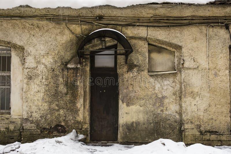 与用雪盖的金属门的一个老被毁坏的大厦 库存图片