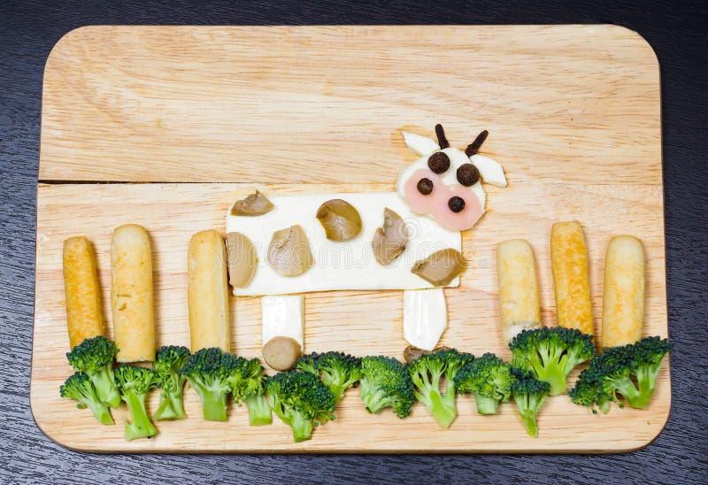 与由乳酪、白色红萝卜、硬花甘蓝、蘑菇和火腿做的风景的母牛,艺术性的食物概念 免版税库存图片