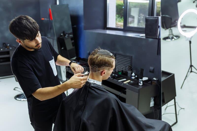 与电剃刀的男性理发 通过使用hairclipper,理发师做客户的理发在理发店 ? 库存照片