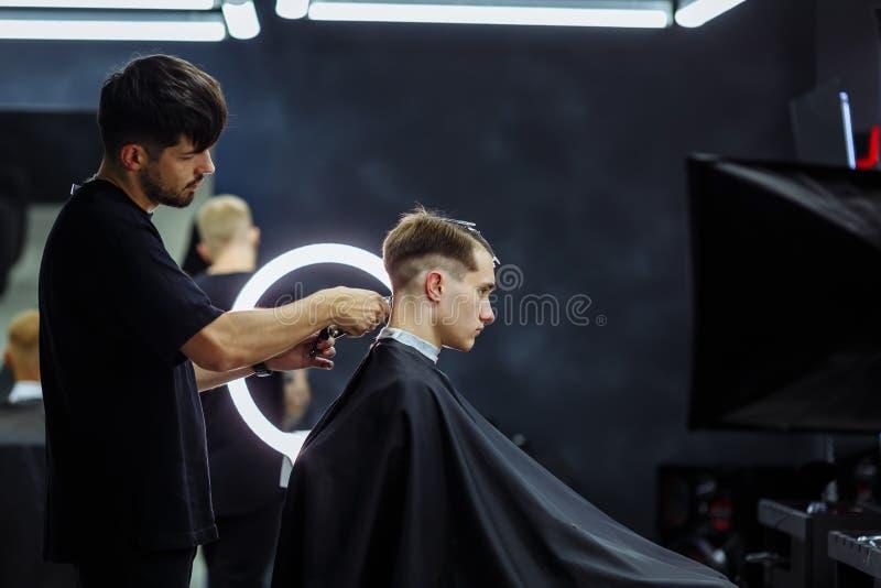 与电剃刀的男性理发 通过使用hairclipper,理发师做客户的理发在理发店 ? 免版税图库摄影