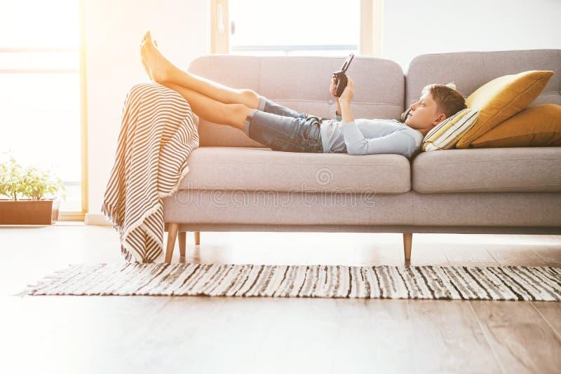 与电子设备的男孩戏剧- gamepad连接用说谎在舒适沙发的智能手机在家庭客厅 免版税库存照片