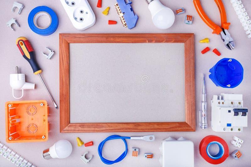 与电工的工具、设备和空间的平的被放置的构成灰色表面上的文本的 家庭修理 图库摄影