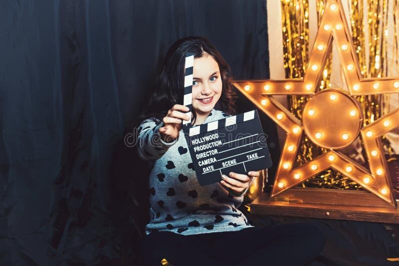与电影拍板或clapperboard的愉快的儿童游戏 女孩微笑在金黄星的电影厂与电灯泡 库存照片
