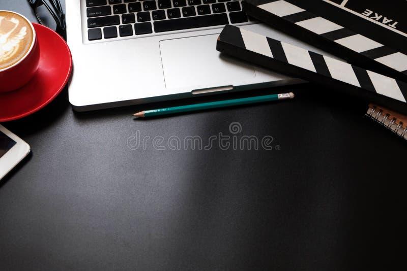 与电影拍板膝上型计算机的办公室材料和咖啡杯写作笔记薄 免版税库存照片