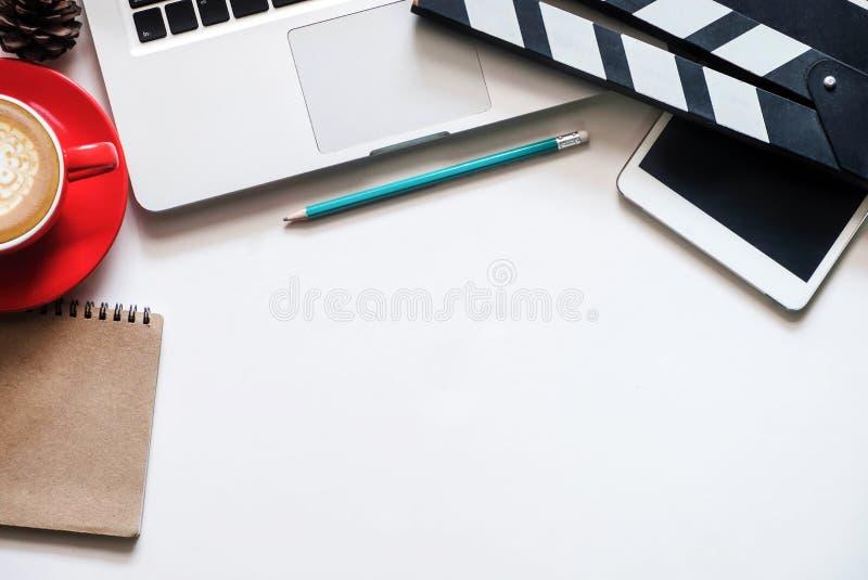 与电影拍板膝上型计算机的办公室材料和咖啡杯写作笔记薄 免版税图库摄影