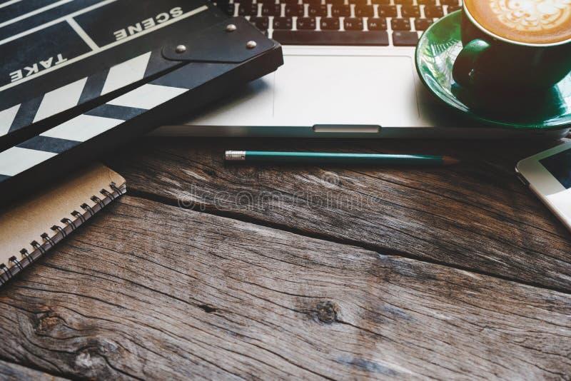 与电影拍板膝上型计算机的办公室材料和咖啡杯写作笔记薄 图库摄影