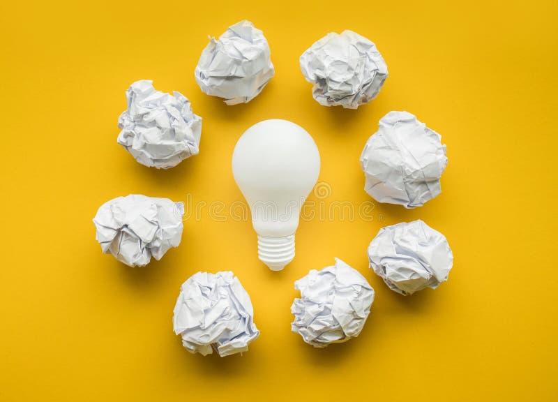 与电灯泡和纸的创造性想法弄皱了球 免版税库存图片