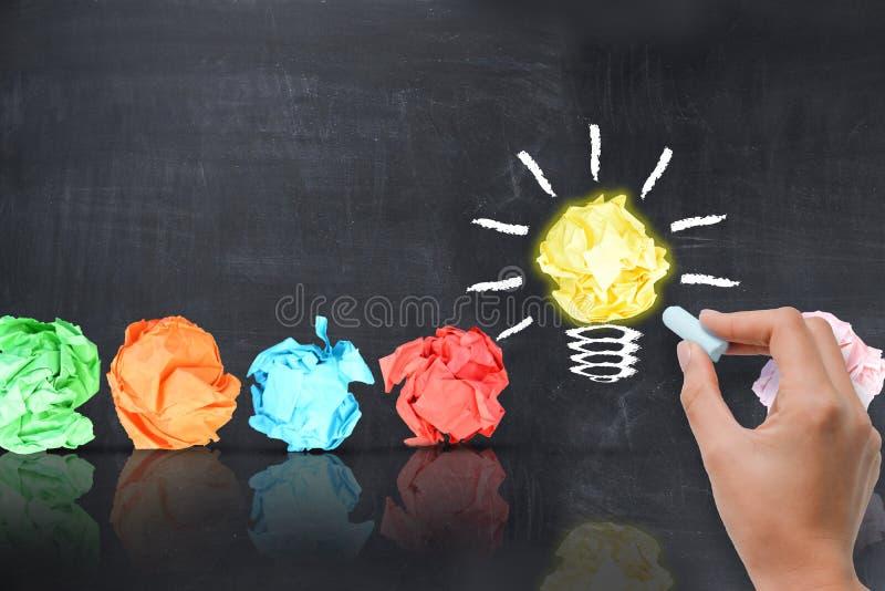 与电灯泡的明亮的想法概念塑造了在黑板的被弄皱的纸 免版税库存照片