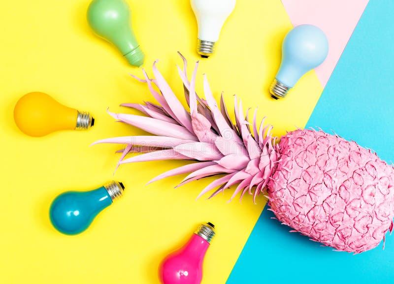 与电灯泡的被绘的菠萝 免版税库存照片