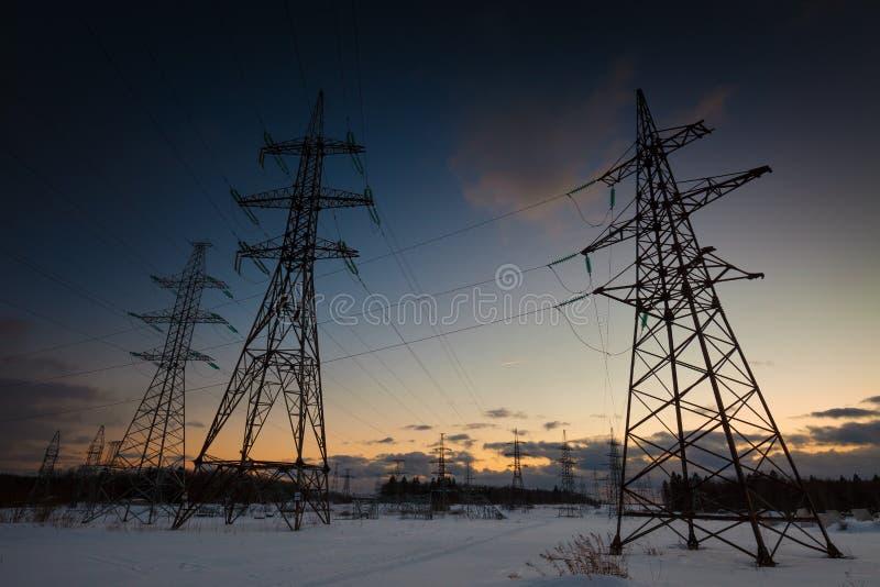 与电线的冬天风景在日落 免版税库存照片