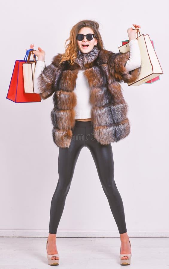 与电视节目预告代码的购物 妇女购物的豪华精品店 女孩穿戴太阳镜和毛皮大衣购物的白色背景 库存图片
