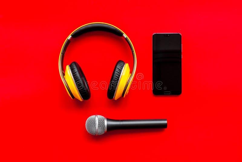与电话、话筒和耳机的播客纪录在文本的红色背景顶视图空间 库存图片