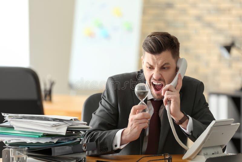 与电话和滴漏的情感商人在桌上在办公室 E 免版税图库摄影