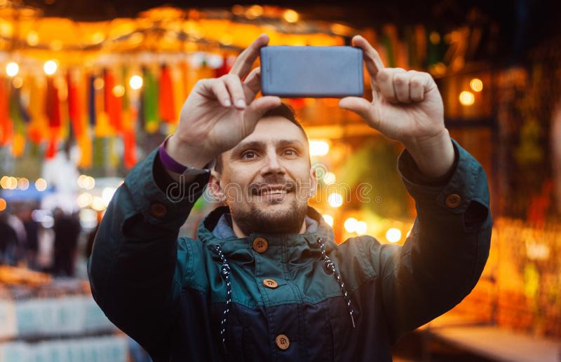与电话的年轻人照相在用五颜六色的旗子装饰的街道上 免版税库存照片