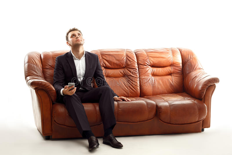 与电话的疲乏的商人坐查寻的沙发 图库摄影