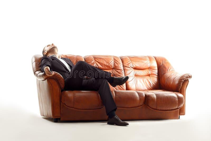 与电话的疲乏的商人坐沙发 库存照片