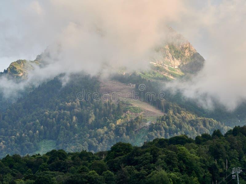 与电车的绿色山坡和在阴暗夏天日落的滑雪坡道 免版税库存照片