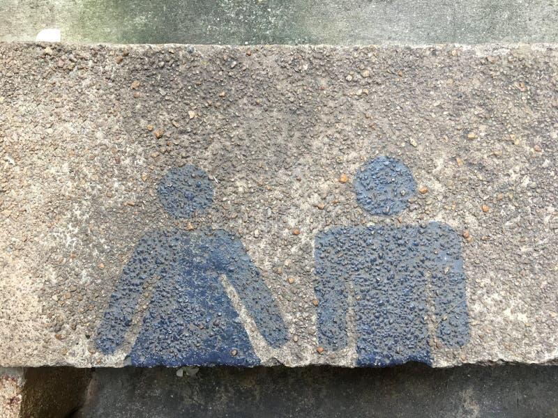 与男人和妇女蓝色绘画的休息室标志在水泥地板上 免版税库存照片