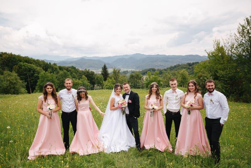 与男傧相和女傧相的新郎和新娘立场 亲吻与朋友的新婚佳偶 o ??  免版税库存照片