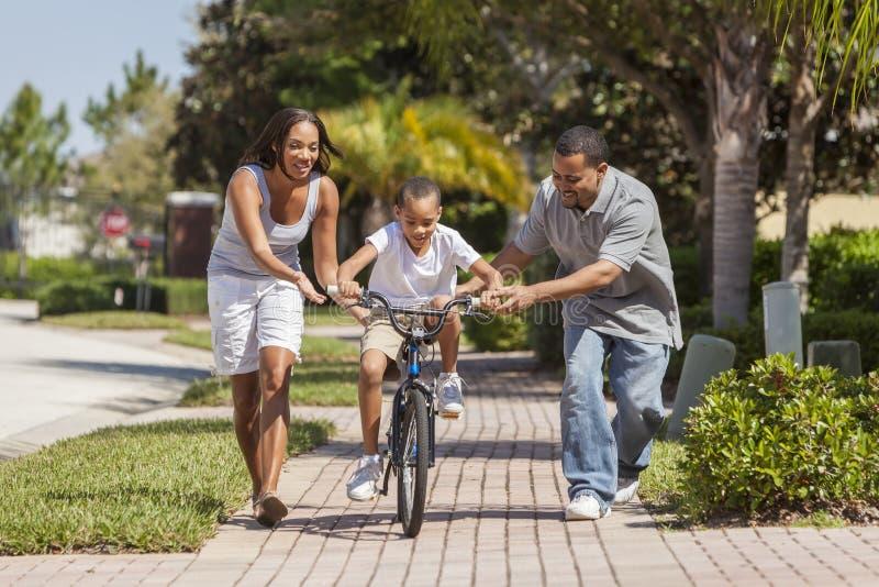与男孩骑马自行车&愉快的父母的非裔美国人的家庭 库存照片