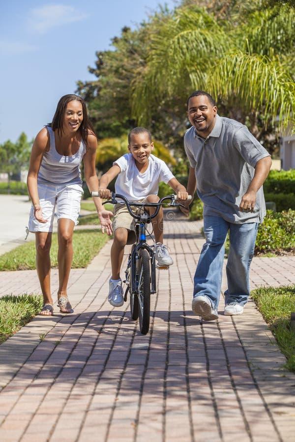 与男孩骑马自行车&愉快的父母的非裔美国人的家庭 免版税库存照片