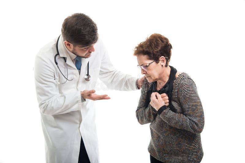 与男性医生的女性资深耐心制造的心脏疼痛姿态 库存照片