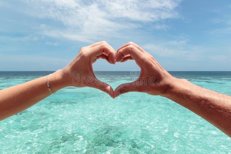 与男性和女性手的心形 作为背景的清楚的大海 在天堂概念的自由 免版税库存照片