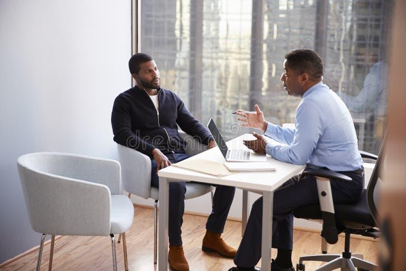 与男性财政顾问关系顾问的人会谈在办公室 免版税库存照片
