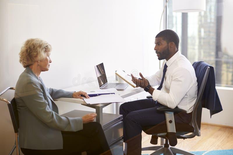 与男性Financial Advisor医生整容外科医生的资深妇女会谈在办公室 图库摄影