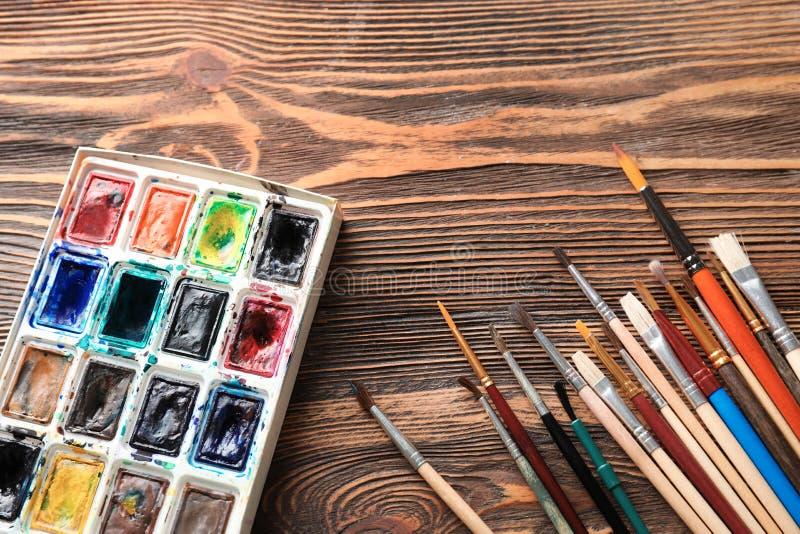 与画笔的水彩在木桌上 免版税库存照片