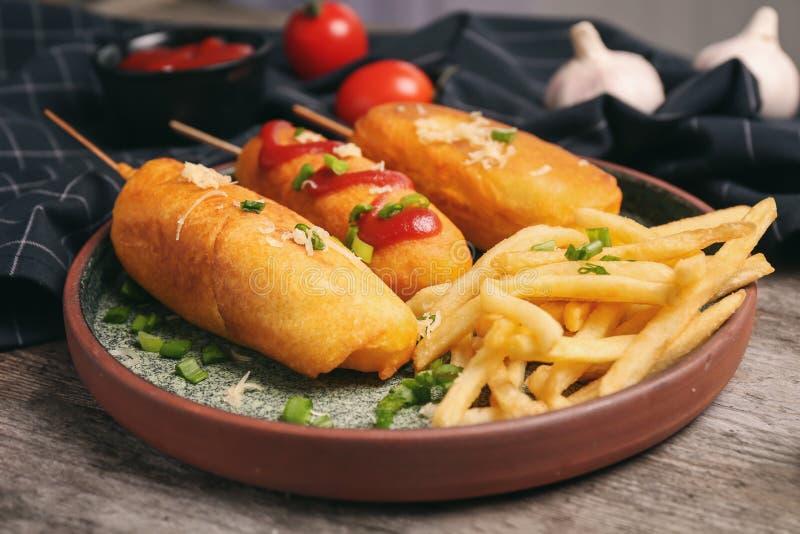 与番茄酱板材的鲜美玉米面热狗 库存照片