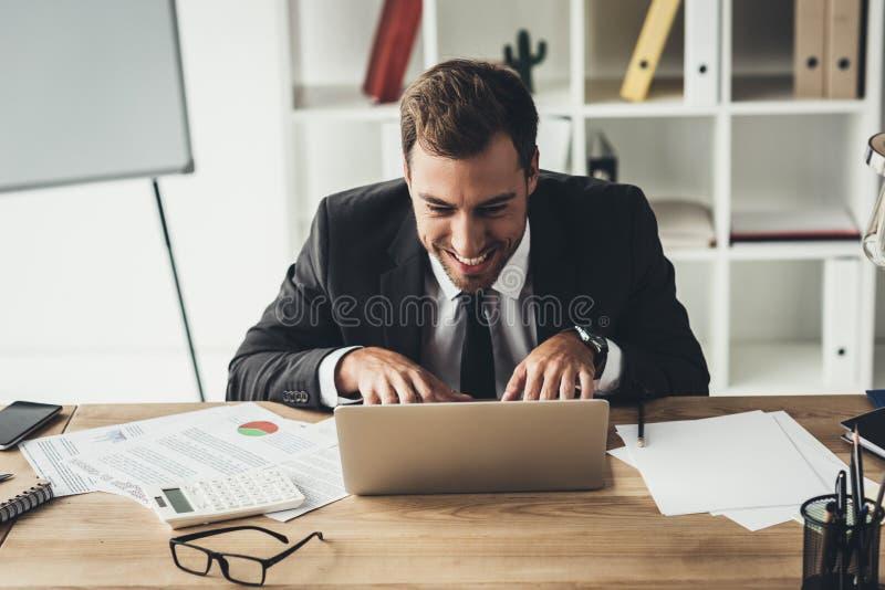 与疯狂面孔鬼脸工作的滑稽的商人 免版税库存照片