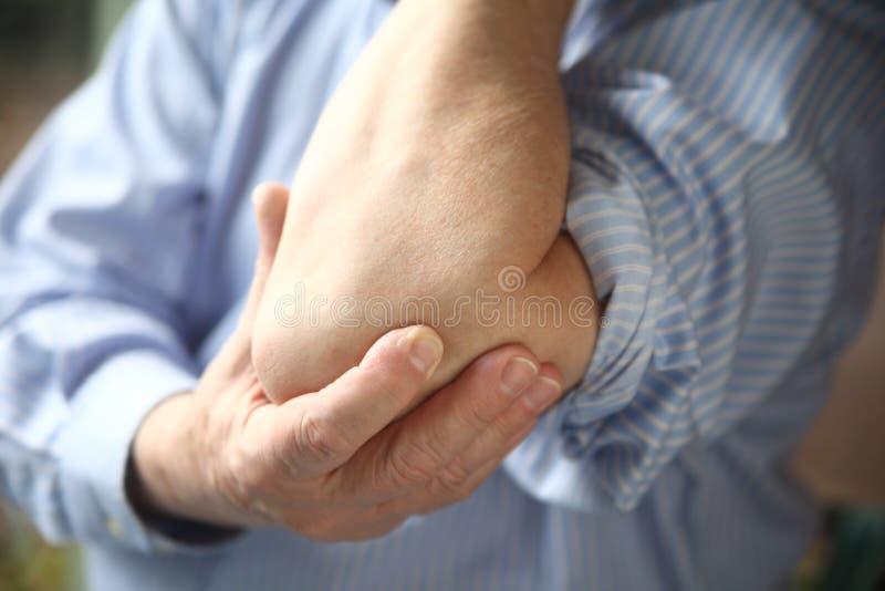 与疼痛手肘的生意人 免版税库存照片