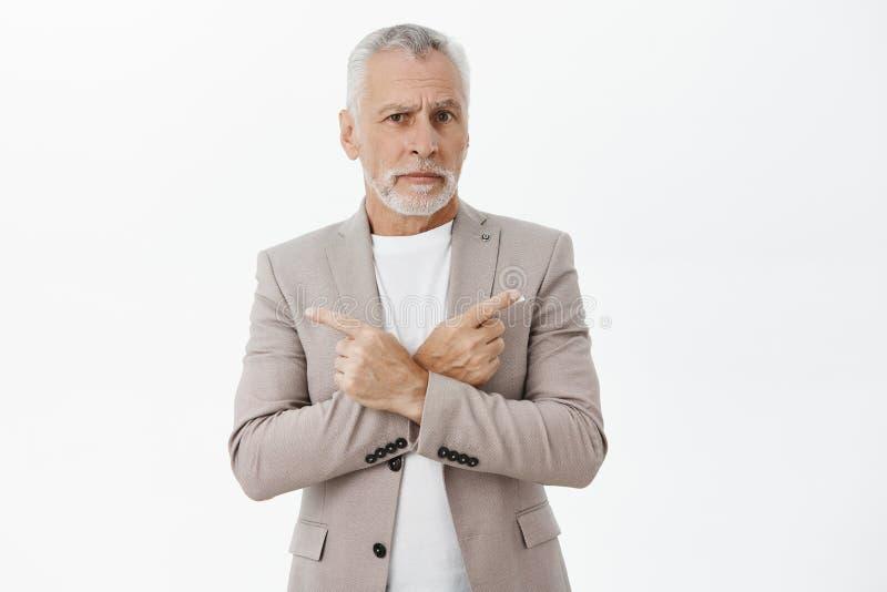 与白发和胡子身分的缺乏信心和被问的英俊的老商人在典雅的正装横渡的胳膊 免版税库存照片