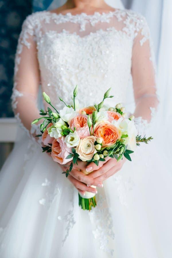 与白玫瑰和桃子牡丹的美丽的新娘花束在白色礼服的新娘手上 婚礼早晨 特写镜头 免版税库存照片