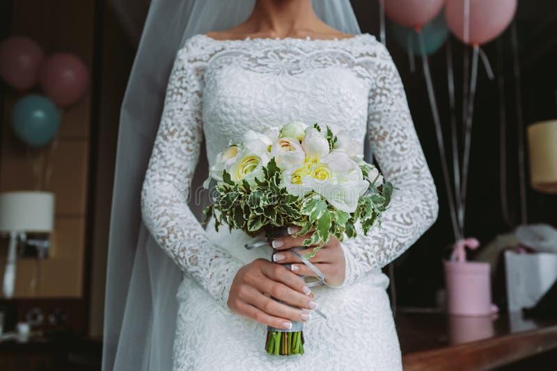 与白玫瑰和牡丹的美丽的婚礼花束 在新娘手上在狭窄,典雅的白色礼服 免版税库存照片