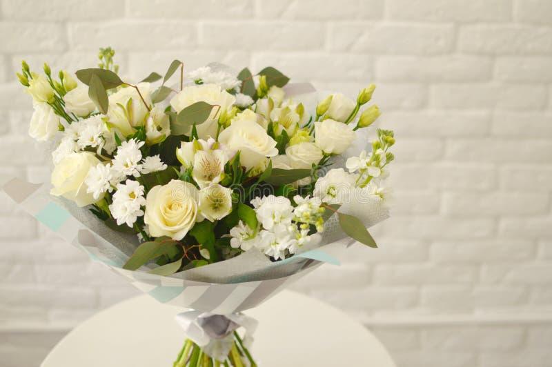 与白玫瑰和camomiles的美丽的花束 图库摄影