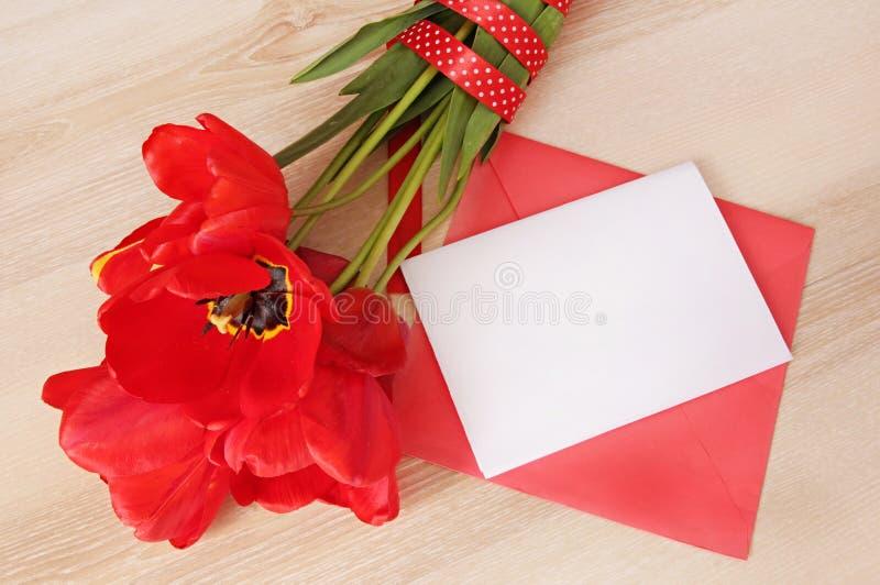 与白皮书card&envelope的红色郁金香花束在木tabl 库存照片