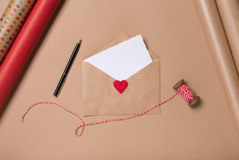 与白纸、笔和红心的工艺信封在米黄背景 概念亲吻妇女的爱人 圣徒华伦泰` s天概念 图库摄影