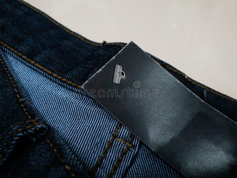 与白纸大模型的黑布料斜纹布标签标记 牛仔布价牌  时尚例证牛仔裤产品销售 库存照片