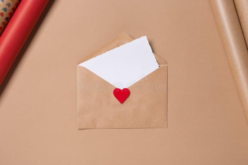 与白纸的工艺在米黄背景的信封和红心 概念亲吻妇女的爱人 圣徒华伦泰` s天概念 母亲` s 免版税库存图片