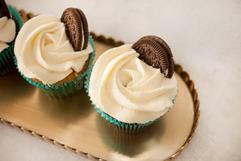 与白色乳酪奶油的杯形蛋糕装饰用在一个黄铜盘子的曲奇饼 图库摄影