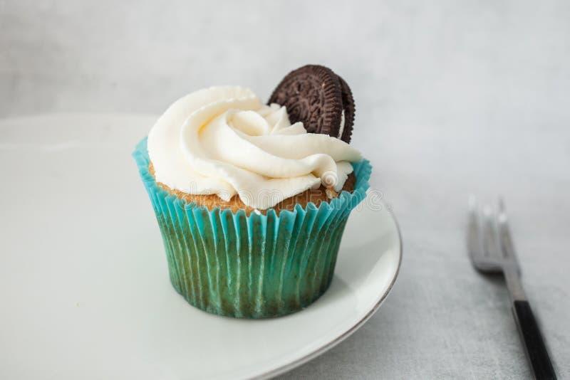 与白色乳酪奶油的杯形蛋糕装饰用在一块白色板材的曲奇饼 库存图片