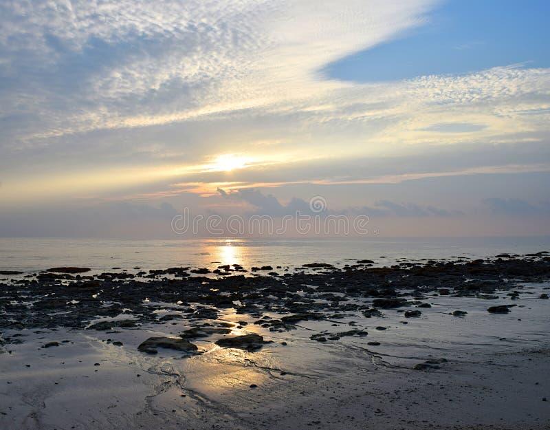 与白色云彩的样式的明亮的金黄阳光在早晨天空的在石海滩-自然本底 免版税库存照片