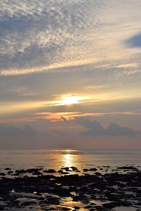 与白色云彩的样式的明亮的金黄黄色阳光在早晨天空的在石海滩-自然本底 免版税库存照片