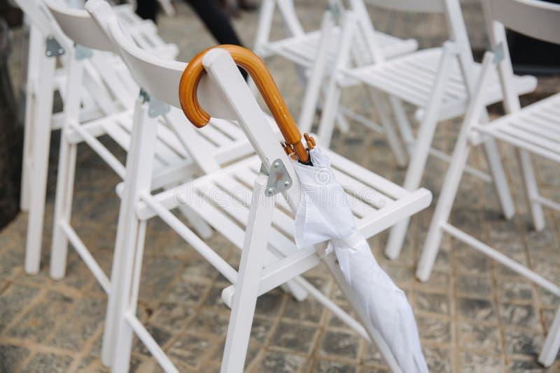 与白色伞的白色椅子 新娘仪式花婚礼 免版税图库摄影