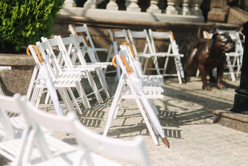 与白色伞的白色椅子 新娘仪式花婚礼 免版税库存照片