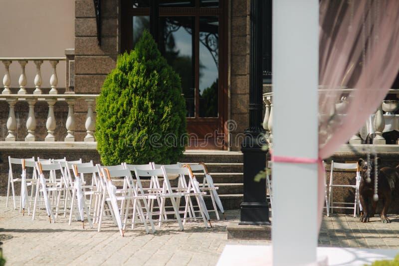 与白色伞的白色椅子 新娘仪式花婚礼 免版税库存图片