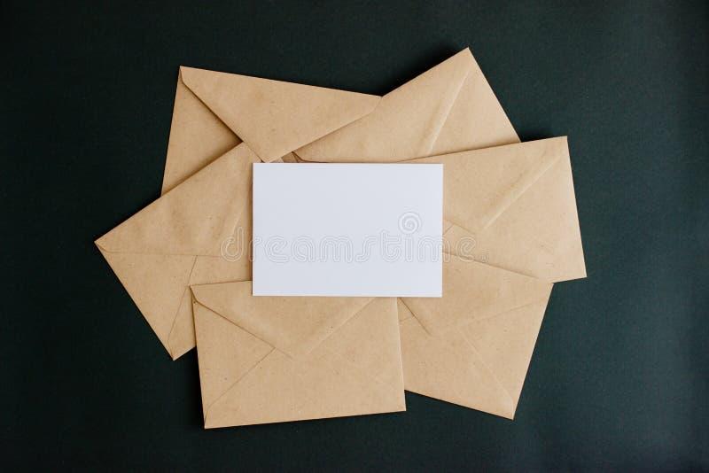 与白色卡片的牛皮纸信封在黑背景 免版税图库摄影